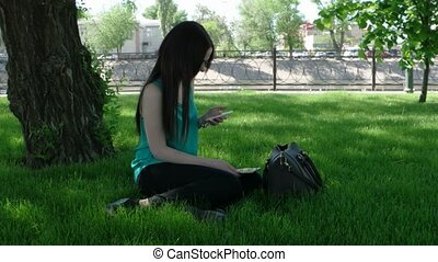 Young women sitting on grass with tablet PC and texting on smart phone