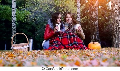 Young women sitting on picnic bundled up in a blanket drinking hot tea from thermos in autumn park. Girls rug near the pumpkin of Halloween theme. 3840x2160