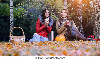 Young women sitting on picnic drinking hot tea from a thermos in autumn park. Girls  rug near the pumpkin of Halloween theme