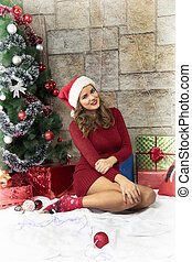 Young women sitting under Christmas tree