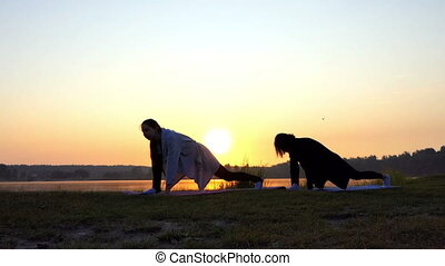 Young Women Stand on Mats ,stretch Out Doing Forward Lunges at Sunset