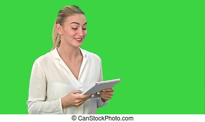 Young women standing with digital tablet presenting the project on a Green Screen, Chroma Key.