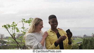 Caucasian and mixed race women hanging out on a roof terrace together on a cloudy day, talking and using a smartphone, taking a selfie, in slow motion