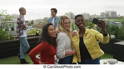 Young women taking a photo of themselves on a roof - Multi-...