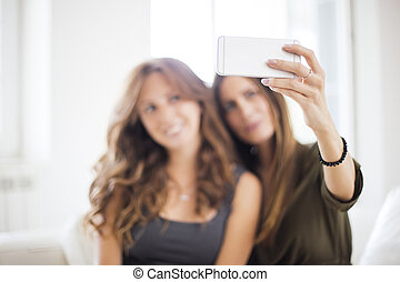 Young women taking selfie in the room
