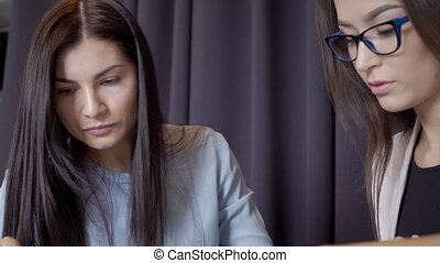 Young women talking while sitting in large company. Two...