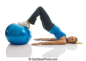 Young women training on a fitness ball. Reverse leg roll...