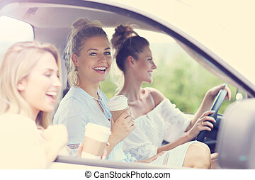 Young women traveling by car with map
