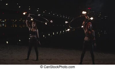 Young women twisting fire hula hoops above head - Skillful...