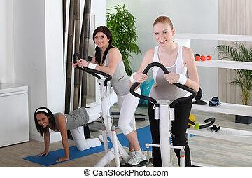 Young women using gym equipment