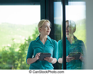 young women using tablet computer by the window