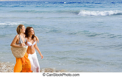 young women walking along beach on spring break or summer vacation