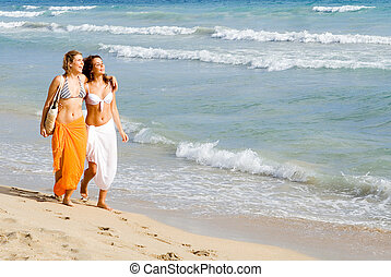young women walking along seashore on beach summer vacation or spring break