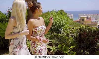Young women walking arm in arm on an outdoor patio pointing...