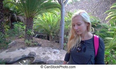 women walking in tropical park - young women walking in...