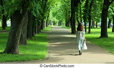 young women walking on the beautiful park with trees