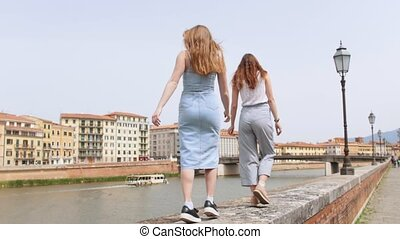 Young women walking on the curb by the river. Mid shot