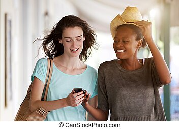 Young women walking together using cellphone