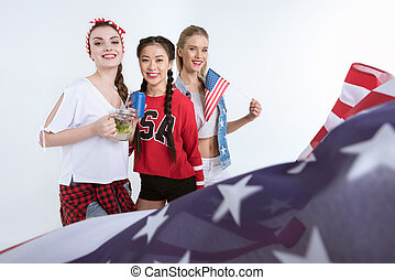 young women with american flag looking at camera and drinking beverages, Independence Day Celebration
