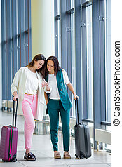 Young women with baggage in international airport walking with her luggage. Airline passengers in an airport lounge waiting for flight aircraft