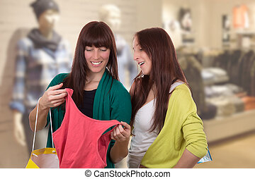 Young women with shopping bags buying clothes in clothing store