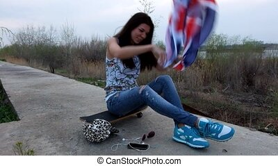 Young women with Union Jack flag sitting with her skateboard on cement lane outdoors