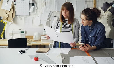 Young women working in design industry are comparing...