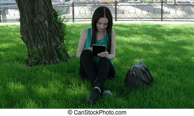 Young women working on tablet PC sitting on grass crossed legs