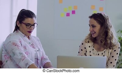 Young women working together in an office.