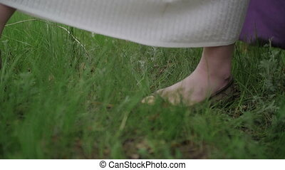 Young Women's Feet Walking on the Grass