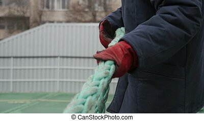 Young worker in a grey sweatshirt and red mitts pulling a rope in a yard in spring