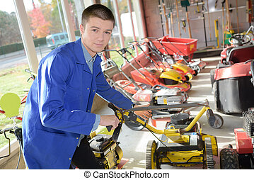 Young worker in lawnmower store