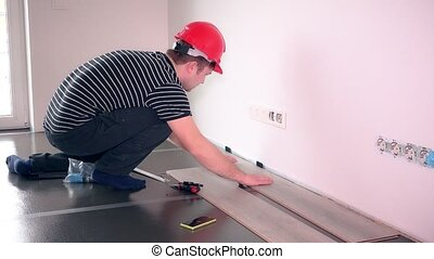 Young worker man laying the laminate floor panels. Static...