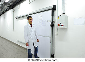 Young worker opening  door of industrial refrigerator