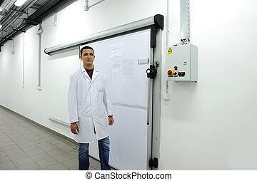 Young worker opening  door of industrial refrigerator