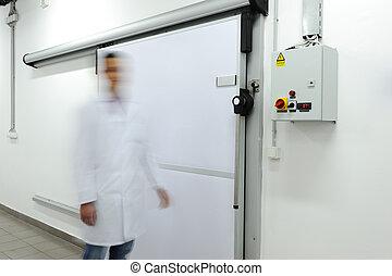 Young worker opening  door of industrial refrigerator, speed motion