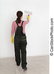 Young worker paint wall in a room to white