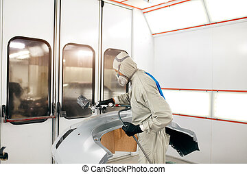 worker painting car parts in special garage, wearing costume...