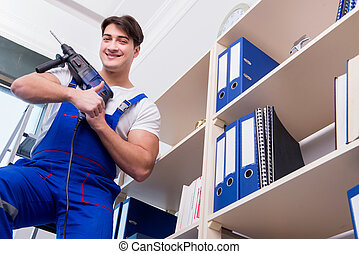 Young worker repairing shelves in office