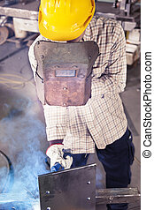 young worker while welding in a steel mill