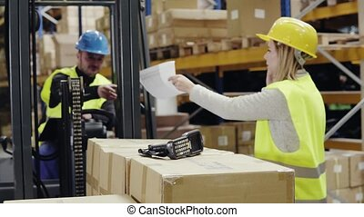 Young workers with smartphone and forklift in warehouse. -...