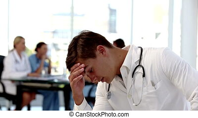 Young worried doctor holding his head besides colleagues...