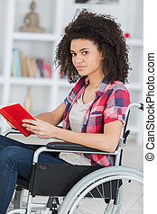 young worried woman in wheelchair holding book
