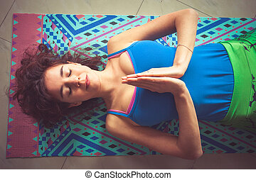 young yoga woman lying on mat with hands in namaste gesture...