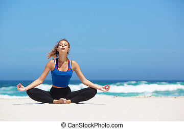Young yoga woman sitting in lotus pose at the beach