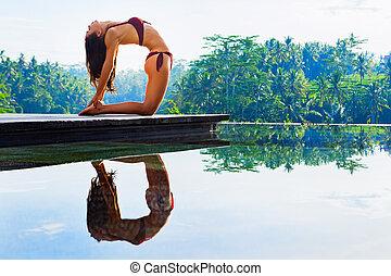 yoga teacher female standing in ustrasana camel posture