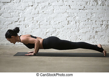 Young yogi attractive woman in chaturanga dandasana pose,...