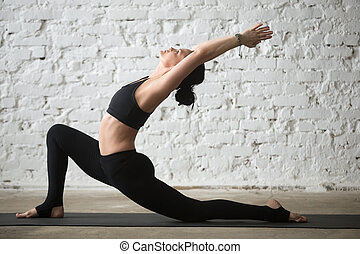 Young yogi attractive woman in Horse rider pose, loft background