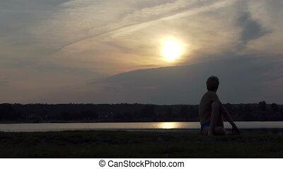 Young yogi sits in an eagle asana on a lake bank in slo-mo
