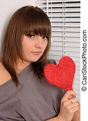 young girl holding the heart in the hands
